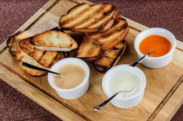 Fatia de torrada assada empanada com queijo e gergelim escorregou em molho sobre uma tábua de madeira