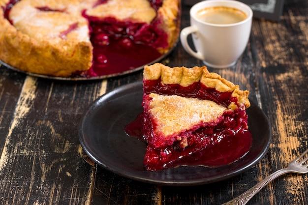 Fatia de torta caseira de cereja, xícara de café, tigela com cerejas e lousa de menu na mesa de madeira