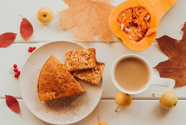 Fatia de torta de abóbora em um prato, uma xícara de café com leite e abóbora.