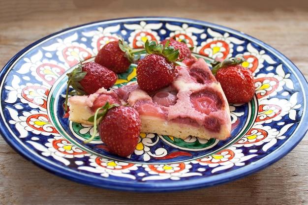 Fatia de torta de morango no prato rosa com morangos