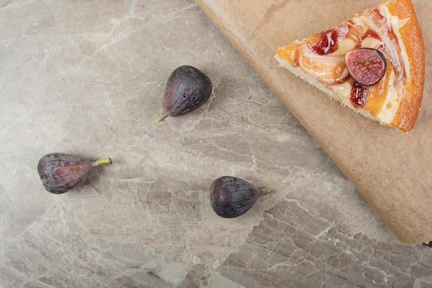 Fatia de torta e figos frescos na placa de madeira. foto de alta qualidade