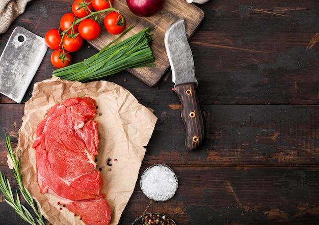 Fatia orgânica crua fresca de refogado de filé de bife em papel de açougueiros com garfo e faca