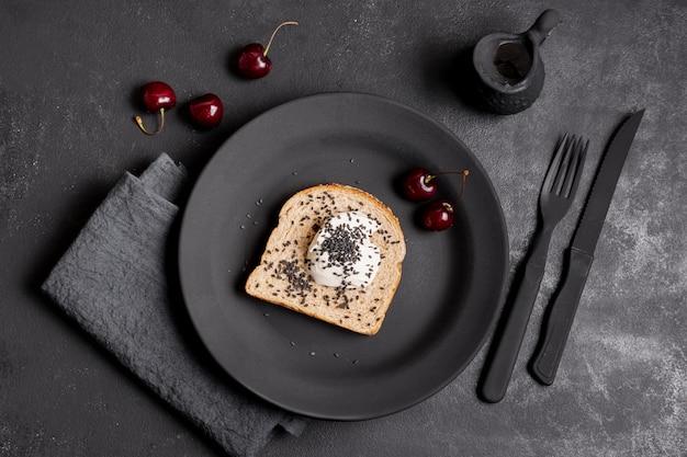 Fatia plana leigos de pão com creme e arranjo de cerejas