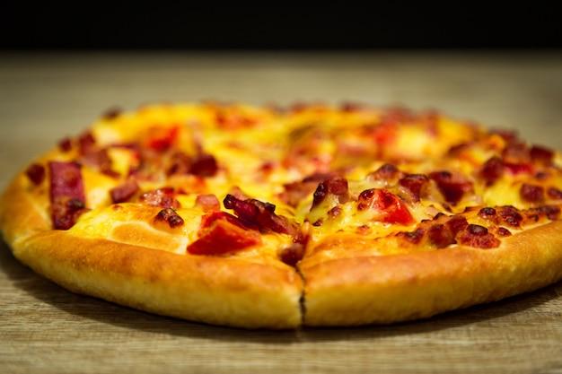 Fatia quente da pizza com queijo de derretimento em uma tabela no alimento do italiano da pizza do restaurante.