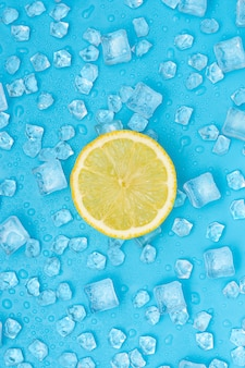 Fatia redonda do limão acima dos cubos de gelo no azul.