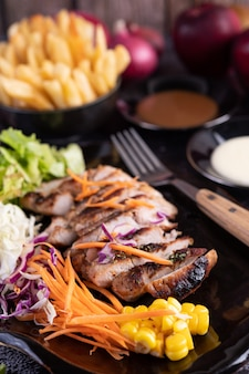 Fatiado bife de porco com pão, cenoura, couve-flor, alface e milho em um prato preto.