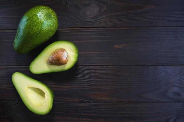 Fatiado e um abacate maduro e bonito em um fundo escuro de madeira com espaço livre à direita