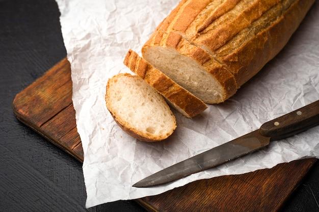 Fatiado em um delicioso pão caseiro em uma tábua de madeira. copie o espaço