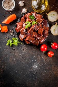 Fatiado, fígado bovino cru com especiarias, ervas e legumes, mesa enferrujada escura cópia espaço vista superior
