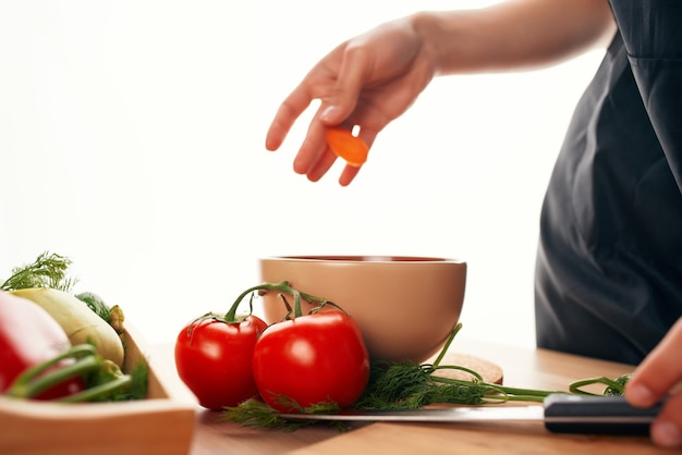 Fatiando cenouras em uma cozinha de tábua de corte, cozinhando vegetarianismo