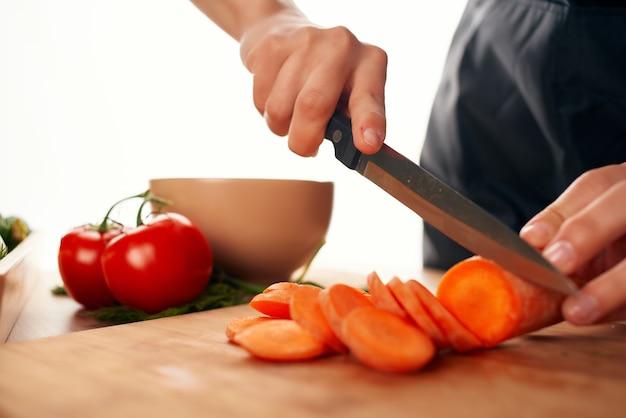 Fatiar cenouras em uma tábua de cortar com uma faca e cozinhar legumes frescos