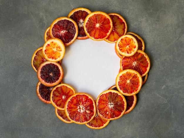 Fatias alaranjadas sicilianos suculentas do sangue no fundo cinzento no quadro do círculo. textura de laranja sangue cortada
