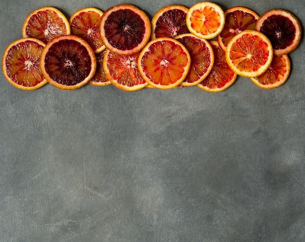 Fatias alaranjadas sicilianos suculentas do sangue no fundo cinzento. textura cortada da laranja pigmentada. fundo cítrico.