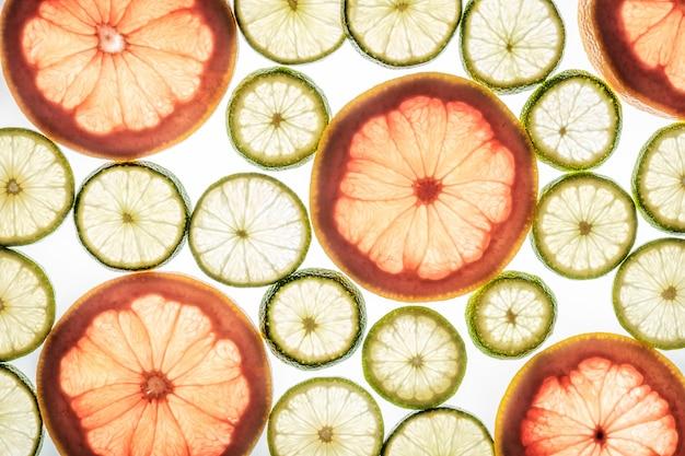 Fatias brilhantes de limão e toranja em branco