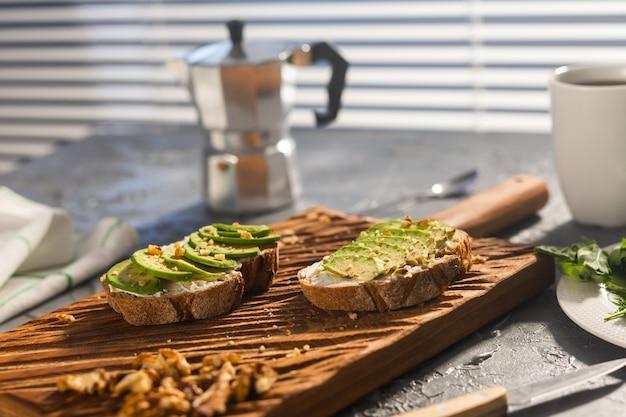 Fatias de abacate em pão torrado com nozes e café da manhã e conceito de comida saudável