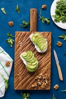 Fatias de abacate na torrada com nozes no café da manhã e conceito de comida saudável, vista de cima, fundo azul