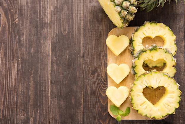 Fatias de abacaxi com um corte em forma de coração com fundo de madeira