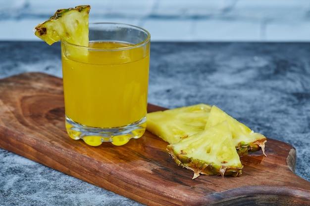 Fatias de abacaxi e suco de abacaxi na placa de madeira.
