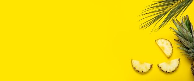 Fatias de abacaxi maduro, abacaxi com folhagem e uma folha de palmeira em um fundo amarelo