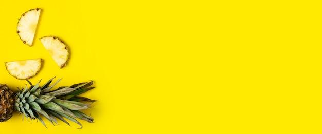Fatias de abacaxi maduro, abacaxi com folhagem em um fundo amarelo. vista superior, configuração plana. bandeira.