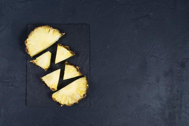 Fatias de abacaxi na placa de pedra preta com espaço para texto