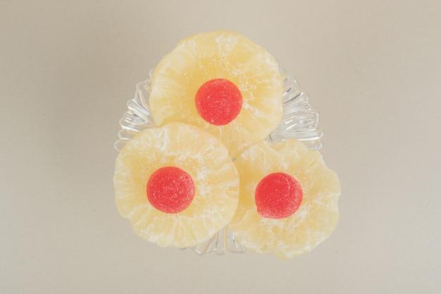 Fatias de abacaxi seco e geleias em prato de vidro