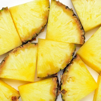 Fatias de abacaxi sobre fundo branco de madeira. textura tropical exótica suculenta fruta saudável. vista superior, plana leigos.