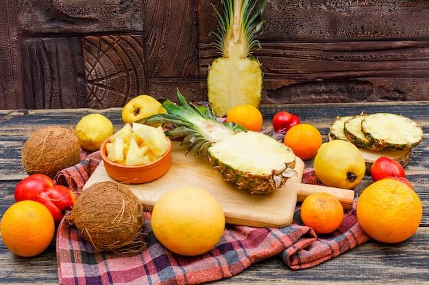 Fatias de abacaxi suculento com cocos, pêssegos, marmelos e frutas cítricas em uma placa de madeira e tigela na superfície de madeira grunge, pano de piquenique e telha de pedra, configuração plana.