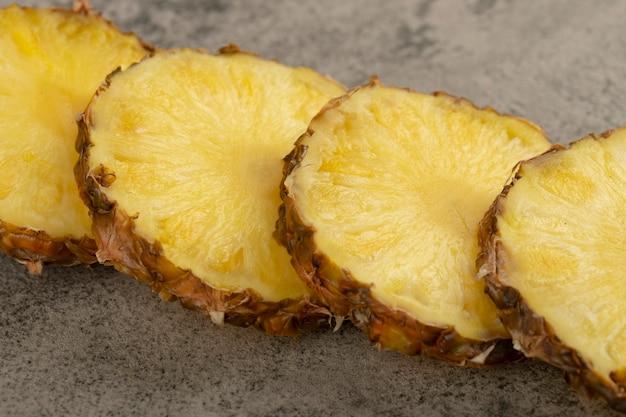 Fatias de abacaxi suculento delicioso colocado na superfície de pedra.