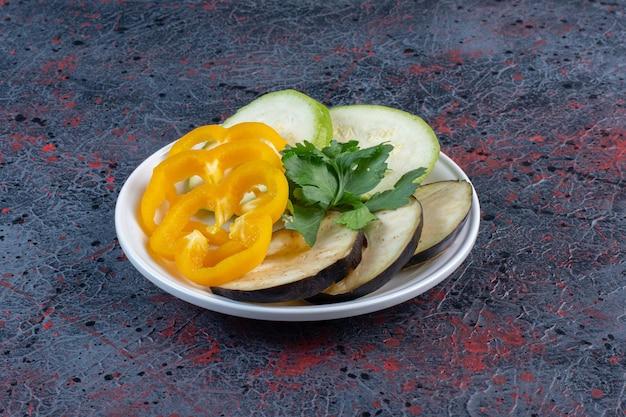 Fatias de abobrinha, berinjela e pimentão com um pequeno molho de salsa em uma travessa com fundo de cor escura. foto de alta qualidade