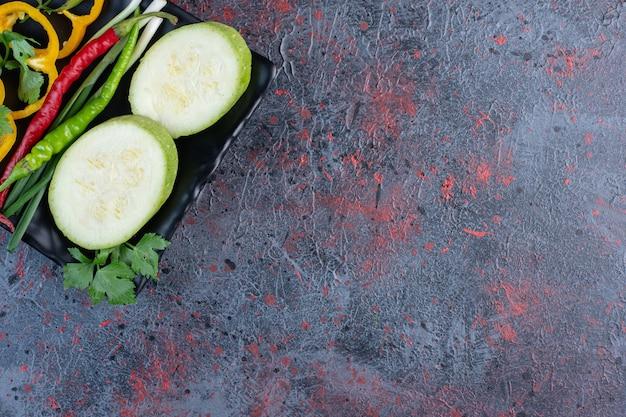 Fatias de abobrinha e pimentão com pimenta e cebolinha em uma travessa na mesa preta.