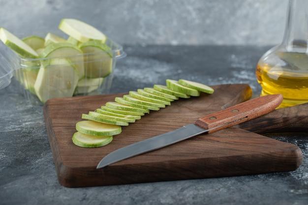 Fatias de abobrinha orgânica fresca na placa de madeira.
