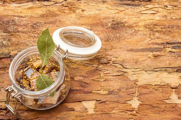 Fatias de arenque com especiarias em uma jarra de vidro.