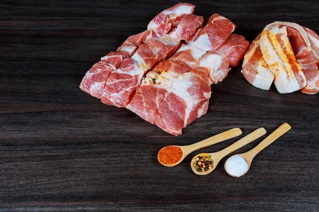 Fatias de bacon cru de carne de porco, rashers, especiarias, pimenta rosa e folhas de alecrim fresco na placa de ardósia preta, close-up,