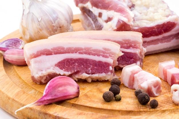 Fatias de bacon e gordura fatiada com pão e alho em uma placa de madeira.