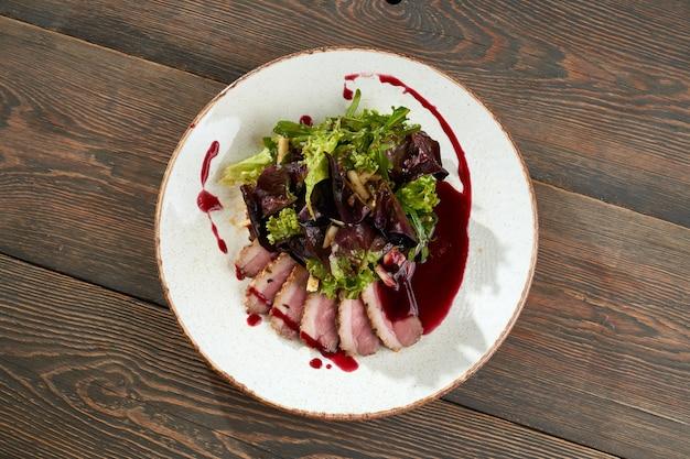 Fatias de bacon servidas com molho de cranberry e alface