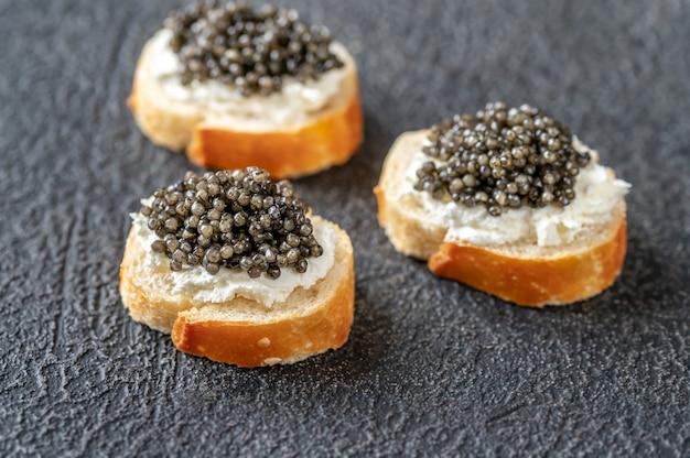 Fatias de baguete com cream cheese e caviar preto
