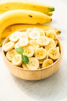Fatias de banana amarela crua na tigela de madeira