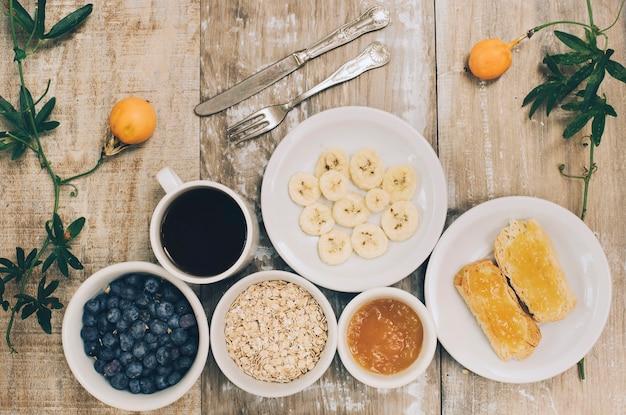 Fatias de banana; aveia; mirtilo; geléia e torradas de pão no cenário de madeira