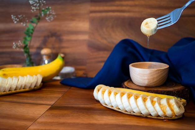 Fatias de banana com mel em uma mesa de madeira