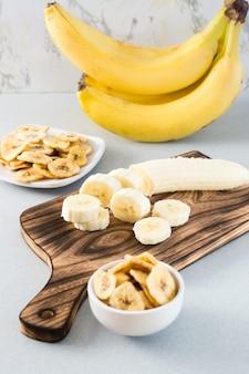 Fatias de banana em uma placa de corte e chips de banana em uma tigela sobre a mesa. comida rápida. visão vertical