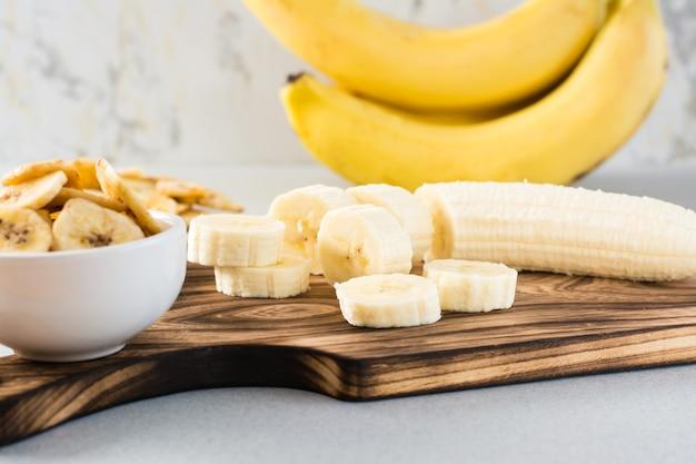 Fatias de banana em uma placa de corte e chips de banana em uma tigela sobre a mesa. comida rápida.