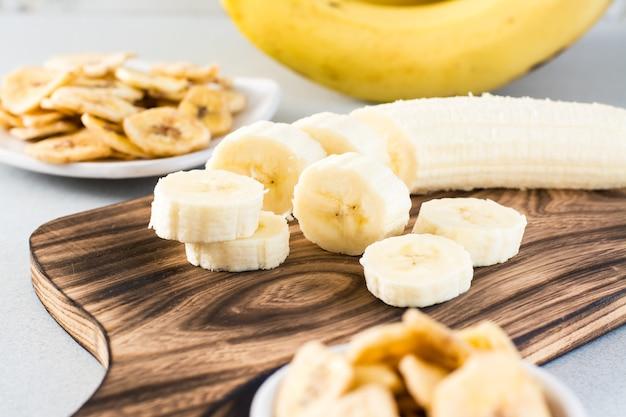 Fatias de banana em uma placa de corte para fazer chips de banana em cima da mesa. comida rápida.