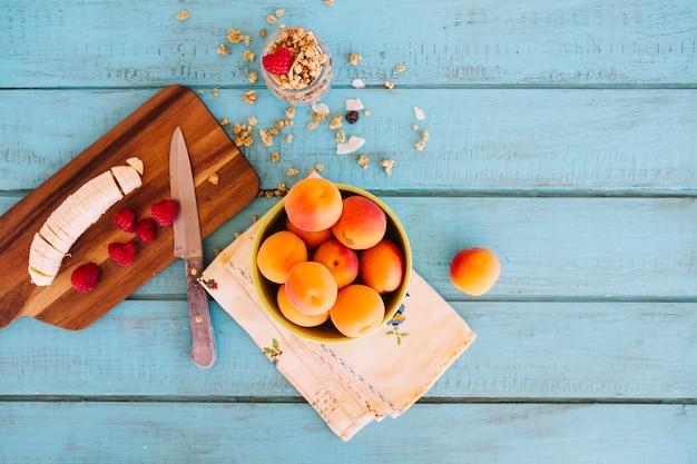 Fatias de banana; morangos; pêssego e aveia na mesa de madeira azul