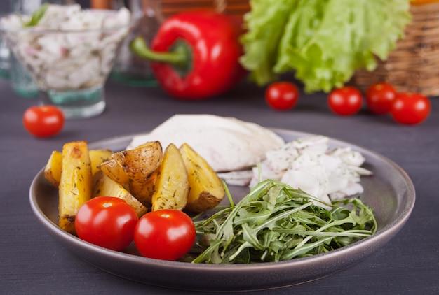 Fatias de batata assada caseira com carne de frango, tomate cereja e rúcula com legumes