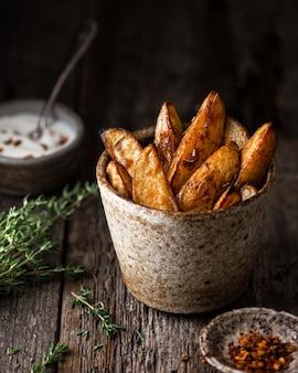 Fatias de batata assada com molho e tomilho em uma xícara de cerâmica sobre fundo rústico de madeira