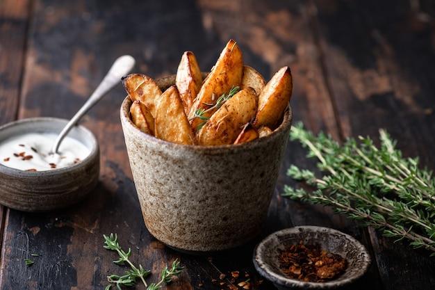 Fatias de batata assada com molho e tomilho em uma xícara de cerâmica sobre uma superfície de madeira