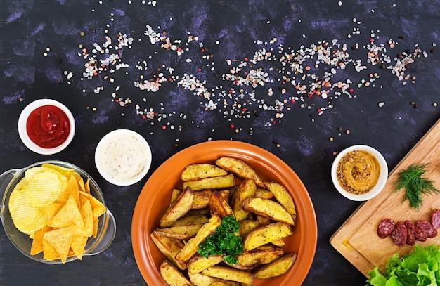 Fatias de batata assada com salsichas e especiarias.
