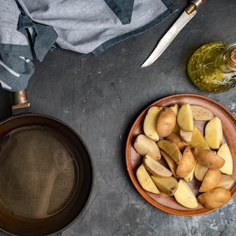 Fatias de batata, frigideira de ferro, faca e óleo