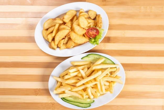 Fatias de batata frita e pauzinhos em um prato. com verduras. para qualquer propósito.